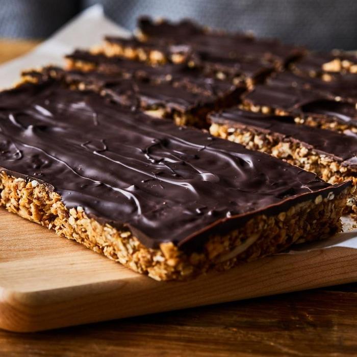 Des barres tendres nappées de chocolat sur une planche de bois.