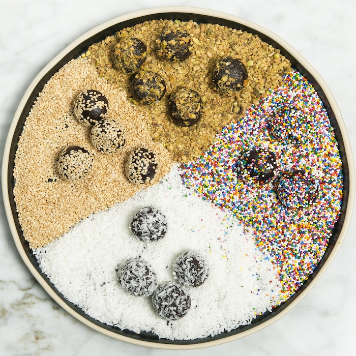 Des boules au chocolat et au tahini réparties dans une assiette comprenant 4 types de garnitures: des graines de sésame, des noix, des confettis de bonbon et de la noix de coco.