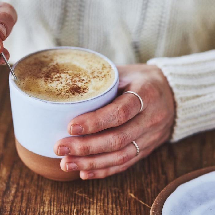 Une main tient un gobelet bleu pâle contenant un café latté à la citrouille et l'autre main tiens une cuillère pour brasser.