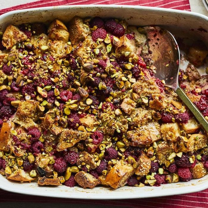 Un plat de pain doré aux framboises et aux pistaches avec une cuillère.