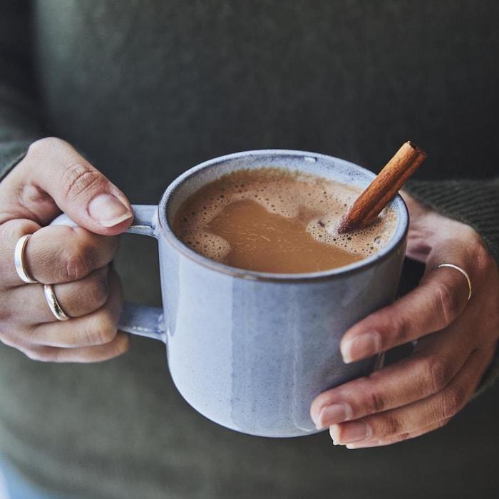 Une personne tient entre ses mains une tasse de thé servie avec un bâton de cannelle.
