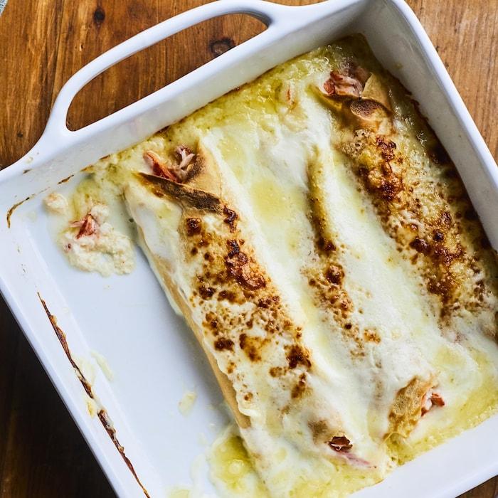 La recette de crêpes au crabe dans un plat blanc carré avec un morceau dans une assiette juste à côté.
