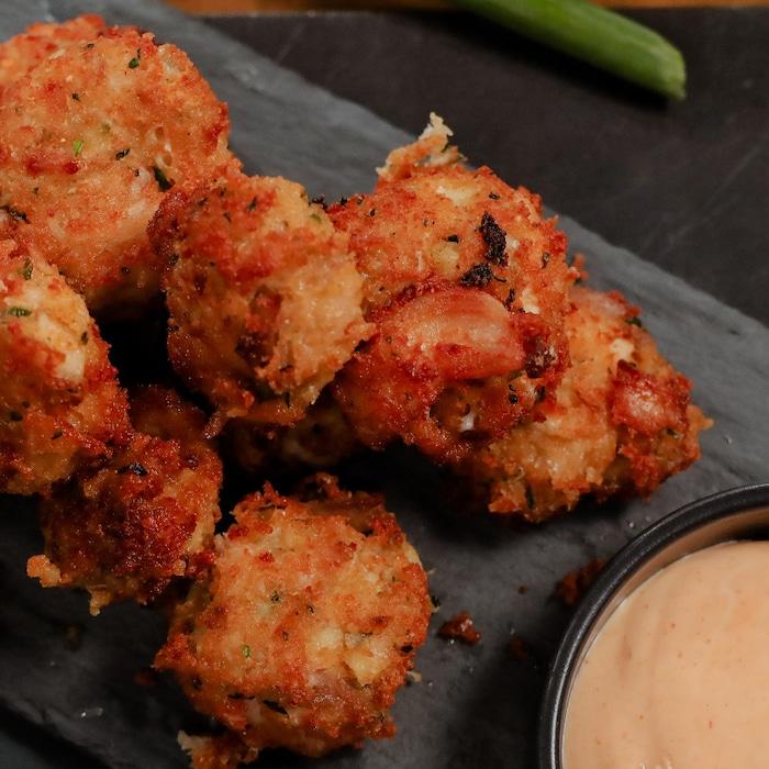 Des croquettes de dinde croustillantes servies sur une ardoise et accompagnée d'une sauce crémeuse.