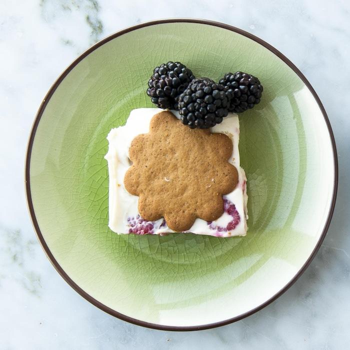 Des parts de dessert étagé servies dans des assiettes et garnies de mûres fraîches.