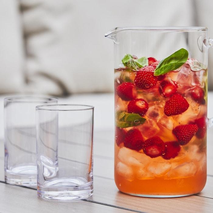 Un pichet transparent avec de l'eau fruitée aux fraises et au basilic avec deux verres vides juste à côté.