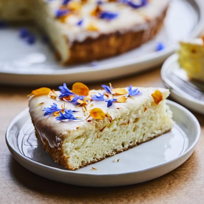 Un morceau de gâteau au citron avec des pétales de fleurs oranges et mauves sur le dessus.