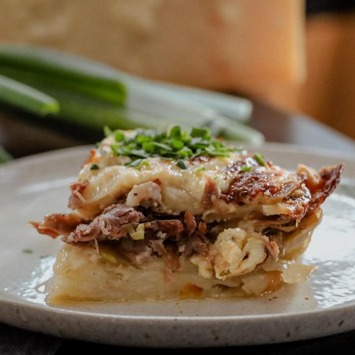 Un morceau de gratin dauphinois au canard confit servi dans une grande assiette.