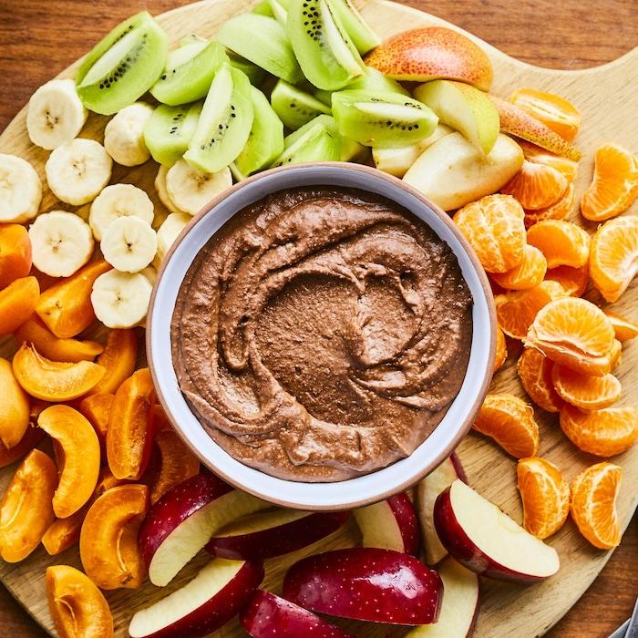 Une planche en bois avec des morceaux de pommes, de bananes, de clémentines, de kiwis et de prunes placés tout autour d'un bol avec du houmous au chocolat.