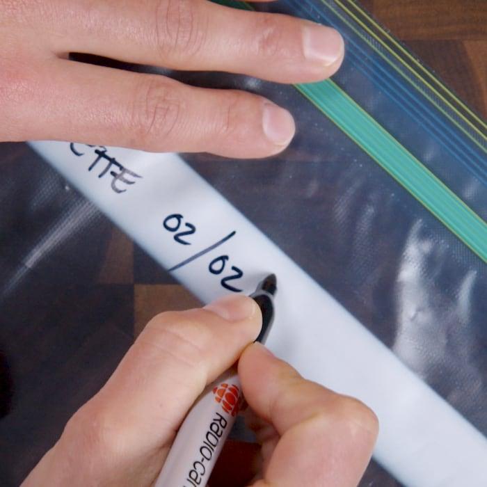 Une personne écrit sur un sac la date à laquelle elle a mis les aliments au congélateur.
