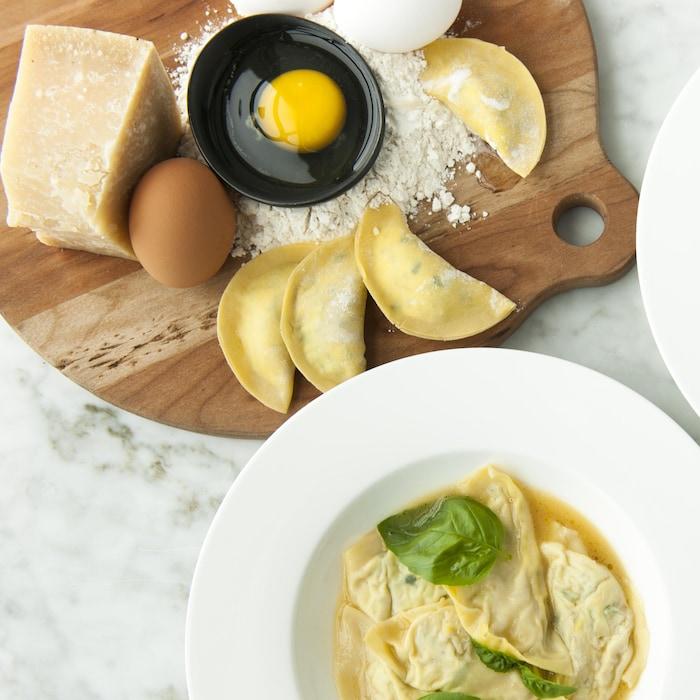 Des mezzalune de ricotta et de courgettes servis dans des bols et nappés de sauce claire.
