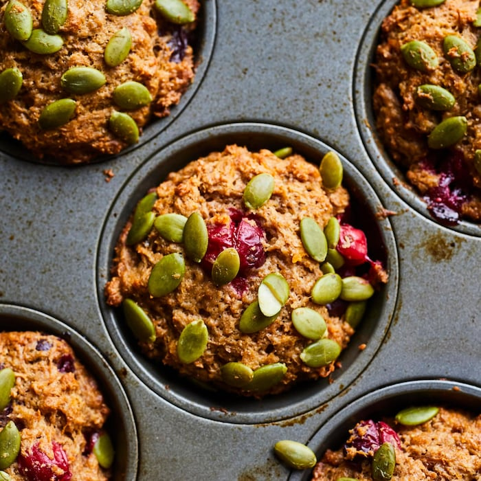 Plusieurs muffins à la patate douce et aux canneberges dans une plaque à muffins, recouvert de graines de citrouille.