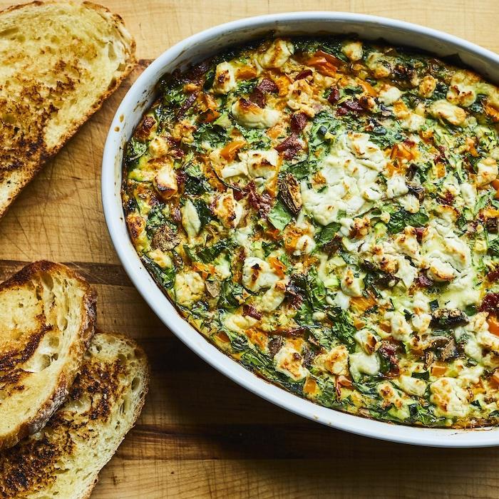 Gros plat rempli d'omelette à partager avec des tranches de pain.