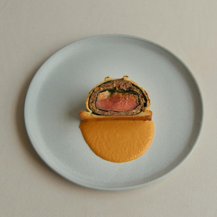 Un morceau de pithiviers au canard est dans une assiette.