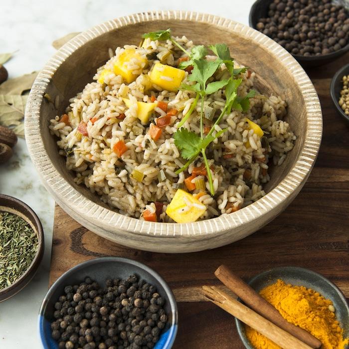 Un plat de riz créole à la mangue, entouré de bols d'épices.