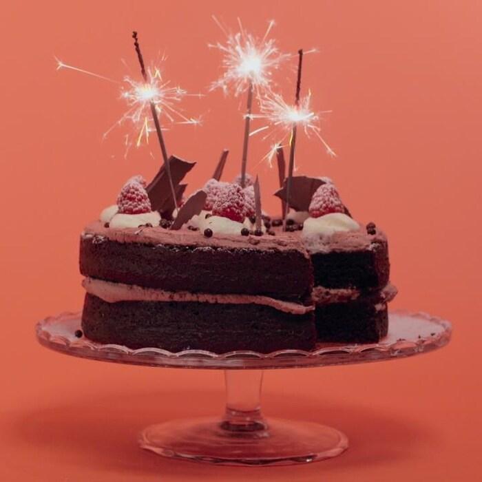 Un gâteau au chocolat avec des bougies scintillantes.