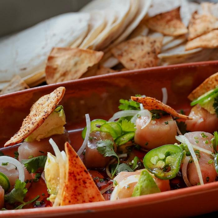 Un bol de salade de thon et d'avocat en dés, le tout garni de tortillas et d'oignons tranchés finement.