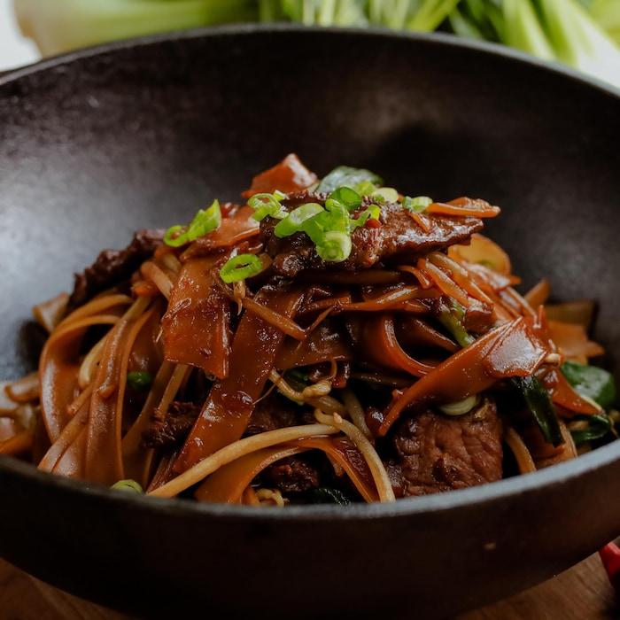 Un sauté de boeuf et de nouilles de riz présenté dans un wok en fonte.