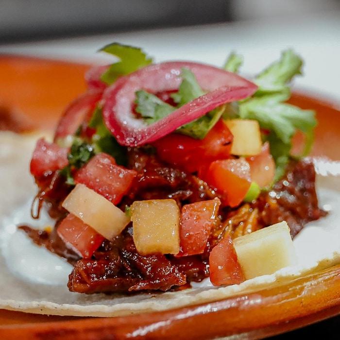 Des tacos d'agneau du Québec garnis de salsa de tomates et cantaloup et de condiments variés.