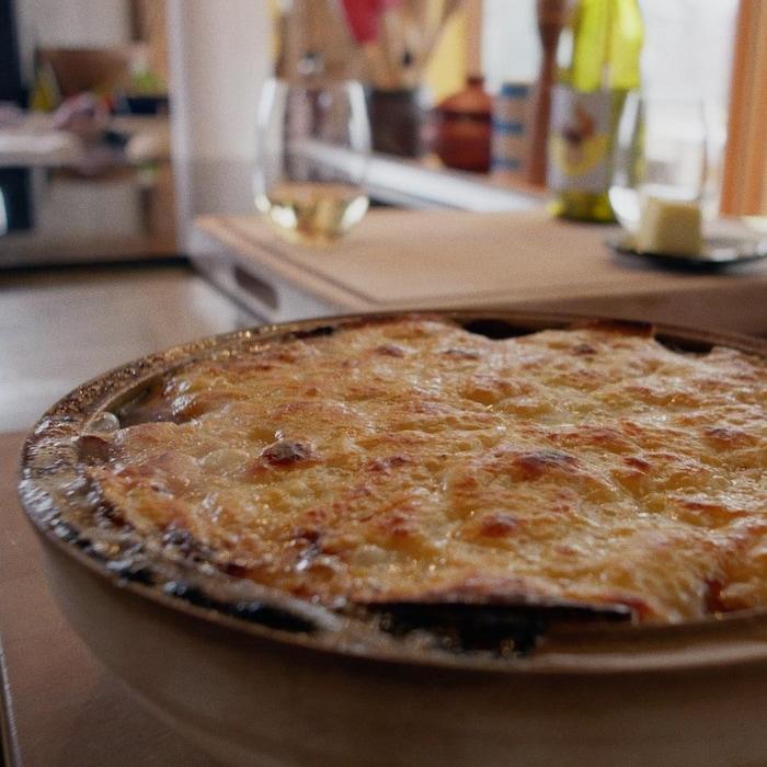 Un plat rond contenant une tartiflette gratinée de fromage.