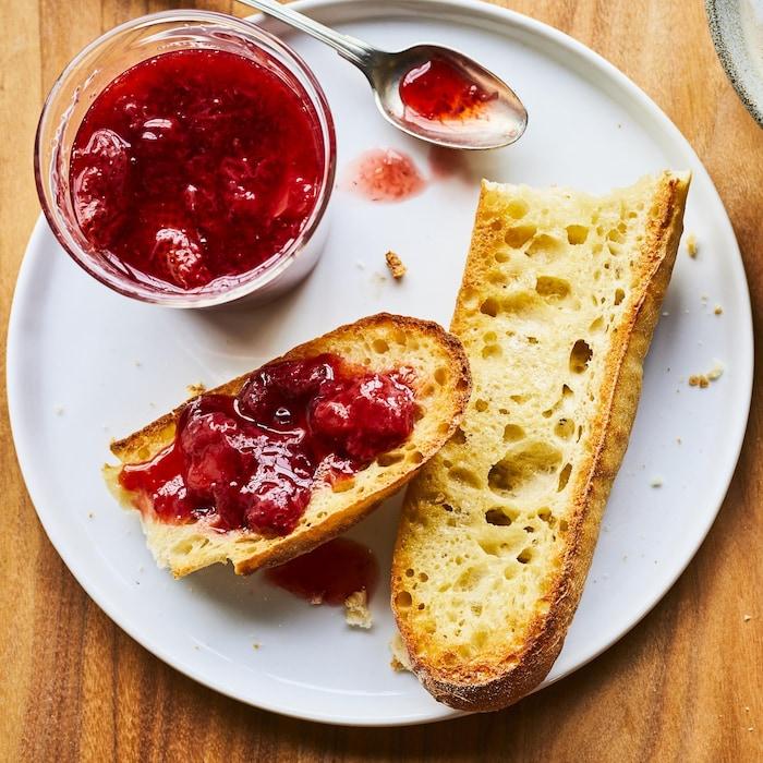 Tartinade aux fraises réduite en sucre sur un pain dans une assiette.