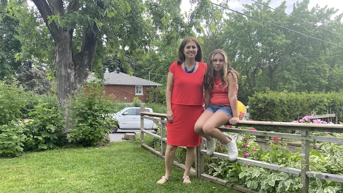 تلميذة ووالدتها في حديقة المنزل.