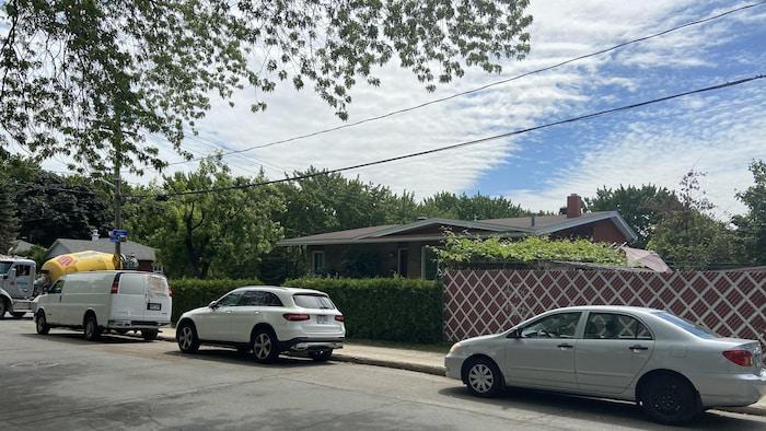 .سيارات مركونة على جانب الطريق أمام منزل تحيط به أشجار