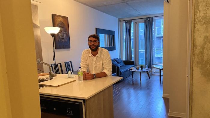 محمّد الغرّاد جالساً إلى عداد المطبخ في شقته السكنية في مونتريال.