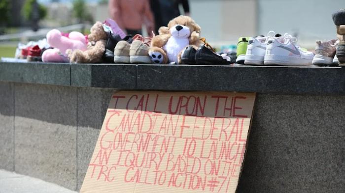 أحذية ولُعَب أطفال ولافتة تدعو الحكومة لإطلاق تحقيق.