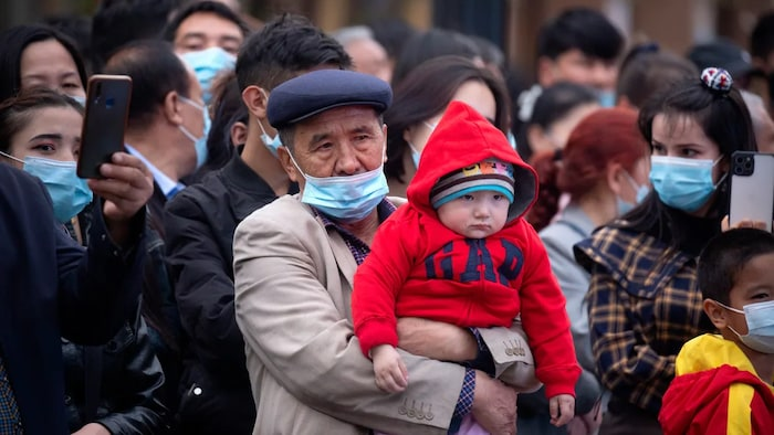 A man holds a child as they watch a dance performance at the International Grand Bazaar in Urumqi in western China's Xinjiang Uyghur Autonomous Region, in April.