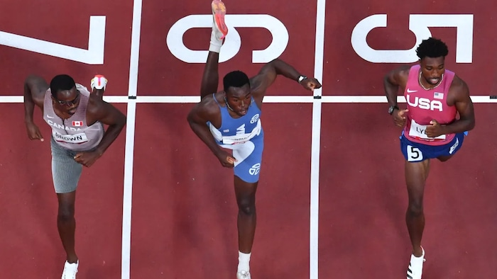 An overview shows, from left to right, Canada's Aaron Brown, Liberia's Joseph Fahnbulle and Noah Lyles of the U.S. crossing the finish line in their men's 200-metre semifinal heat on Tuesday at the Olympic Stadium. Brown won the heat in 19.99 seconds.