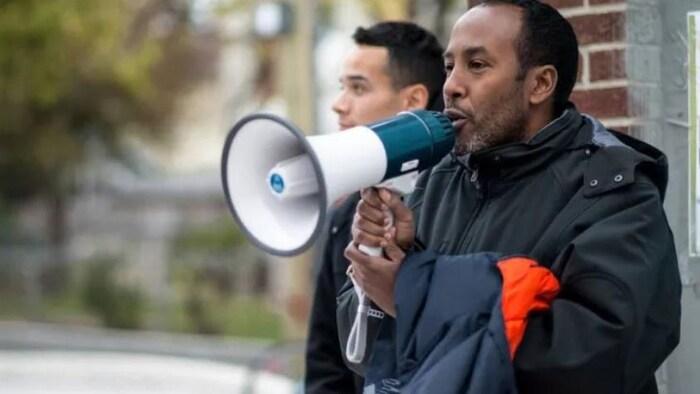 Abdikheir Ahmed sostiene un megáfono en sus manos. Está de pie frente a una pared de ladrillos.