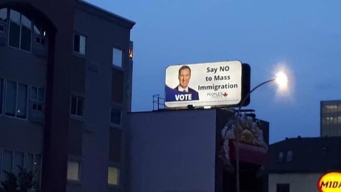 """Un cartel con la imagen de Maxime Bernier denunciando la """"inmigración masiva"""" en una calle de Regina, en la provincia de Saskatchewan."""