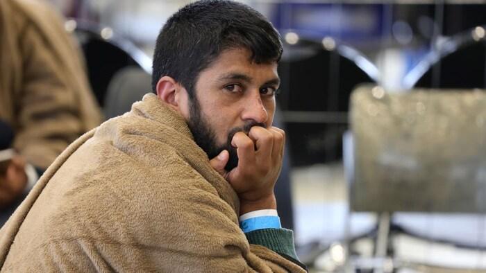 2021 年 8 月 26 日,在美国 Ramstein 空军基地,一名从阿富汗撤离的男子坐在临时值机大厅,等待登机前往美国达拉斯市。