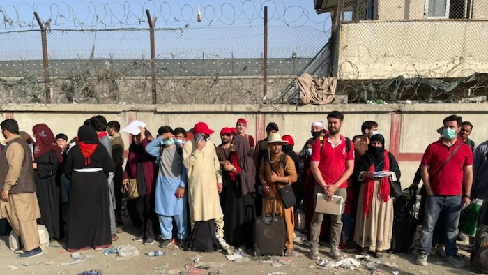 Afghan men and women with suitcases waiting to be evacuated, standing by a concrete wall with barbwire.