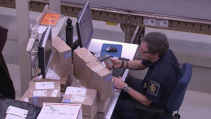 Un agent des services douaniers numérise des colis.