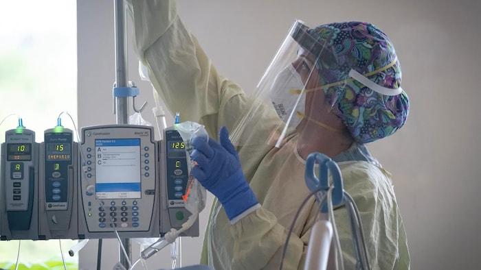 Un empleado del personal médico con bata y mascarilla N95 cambia las bolsas de líquido intravenoso en un hospital de Alberta.