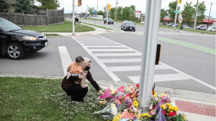 Nafisa Azima carries Seena Safdari while laying flowers at the fatal crime scene where a man driving a pickup truck jumped the curb and ran over the Muslim family.
