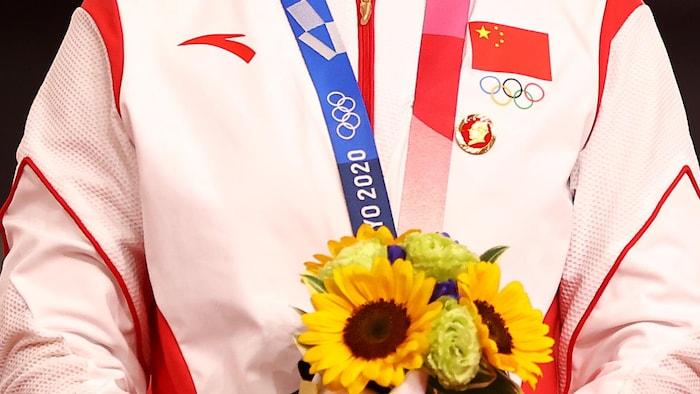 Une épinglette à l'image de Mao Zedong attachée au vêtement d'une cycliste chinoise qui tient un bouquet de fleurs.