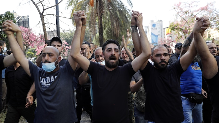 متظاهرون يرفعون أيديهم ويطلقون هتافات.