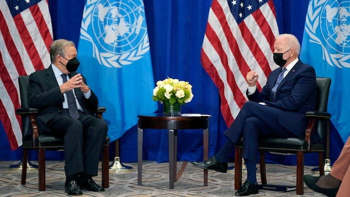 U.S. President Joe Biden met with UN Secretary General Antonio Guterres. They are both sitting on chairs, with a small table between them. United Nations and American flags in background.