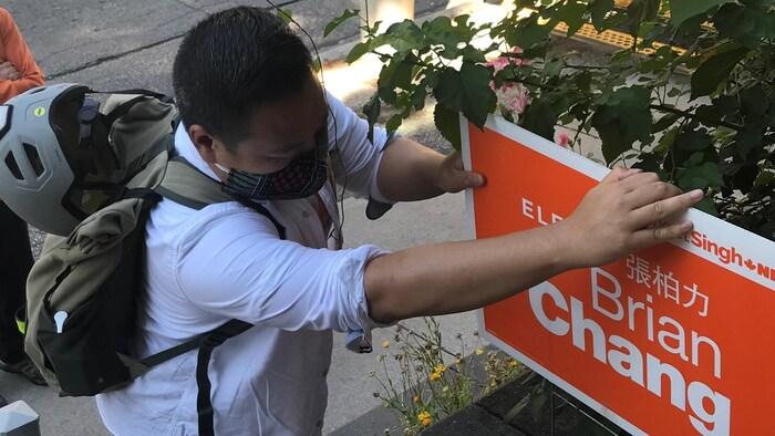 征得同意,张柏力把宣传牌插在选民花坛中。