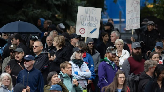 Protesters met at Olympic Plaza, where some speakers shared misinformation about COVID-19 case counts and the accuracy of PCR tests, before marching through downtown. (Brooks DeCillia/CBC)