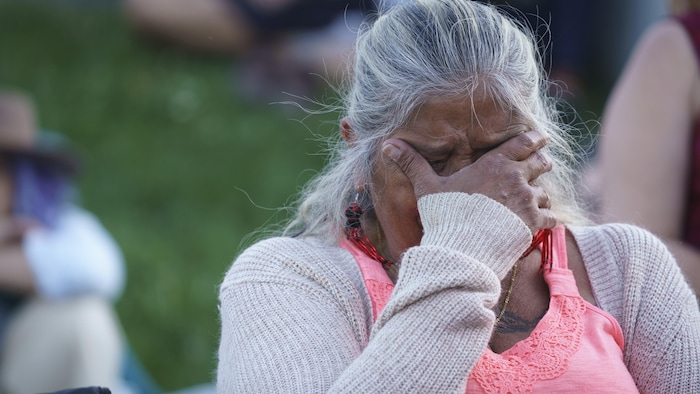 Una mujer que llora se sujeta la cabeza con la mano derecha.