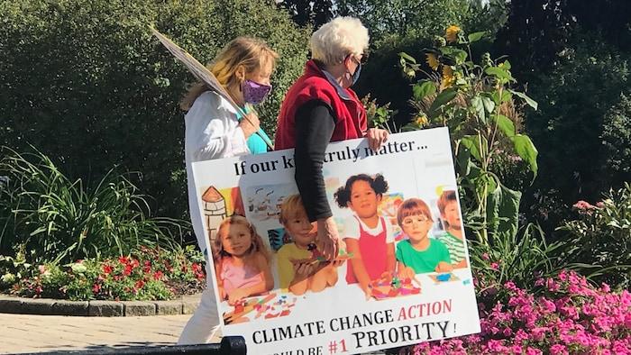 乔治镇,举着标语呼吁气候变化行动的抗议者。