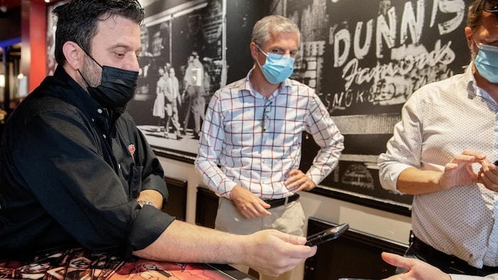 Jimmy Staveris, manager of Dunn's Famous restaurant scans the COVID-19 QR codes of customers in Montreal earlier this month as the Quebec government's COVID-19 vaccine passport came into effect.