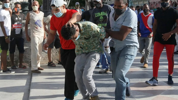 A person is detained during protests in Havana on Sunday. The protests also brought out those who support the Cuban government.