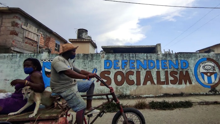 People ride by graffiti declaring 'Defending Socialism' in Havana on Monday, where the scene was calm after the previous day's vocal protests.