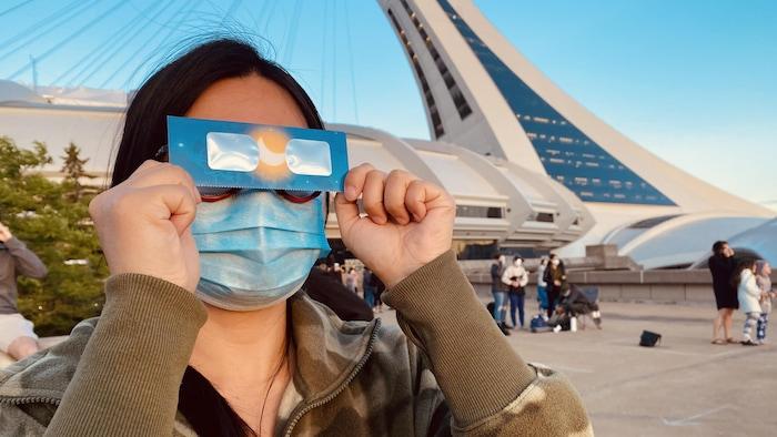 Une femme protège ses yeux avec des lunettes spéciales pour observer l'éclipse près du stade.