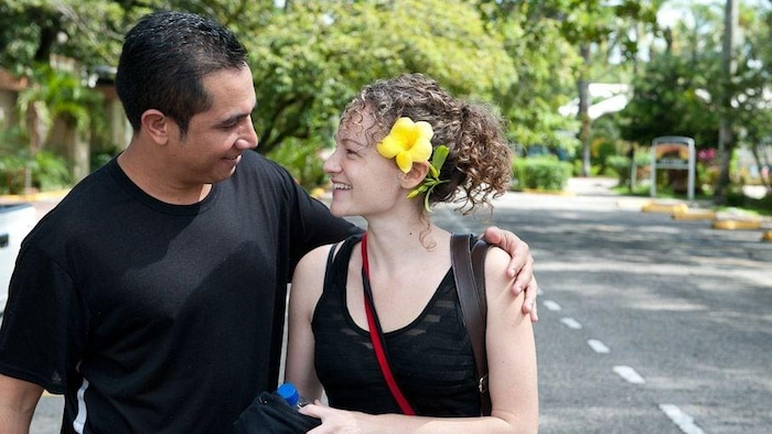 Espinal with his arm around the shoulders of his wife, Karen Spring, standing on a road lined with trees in Honduras.