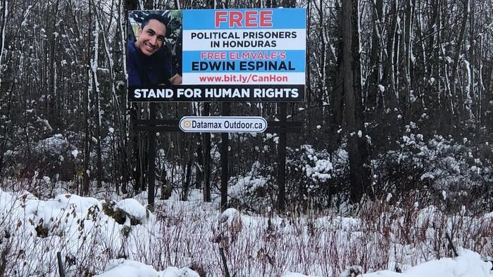 """Un cartel publicitario frente a un bosque cubierto de nieve muestra la imagen de Edwin Espinal con las palabras """"Free Political Prisoners in Honduras - Free Elmvale's Edwin Espinal - Stand for Human Rights"""""""